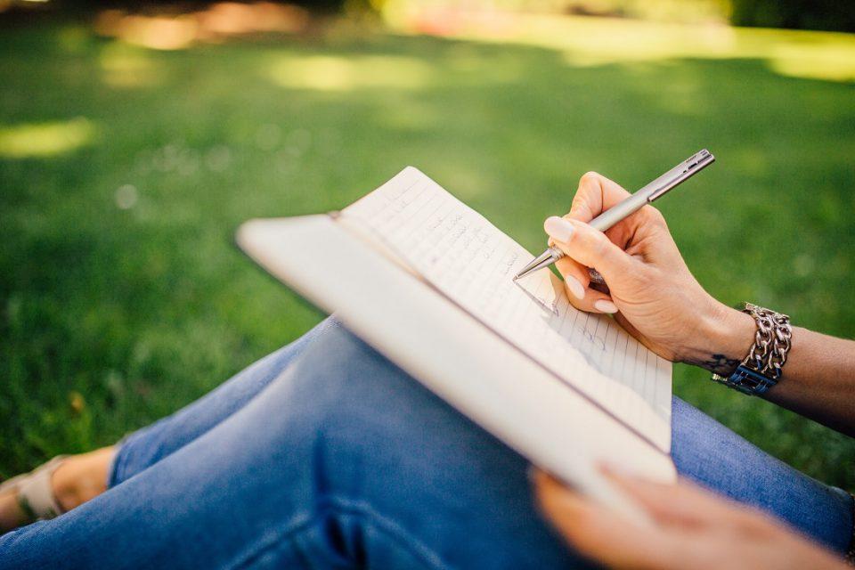 Donna-scrive-seduta-sull'erba